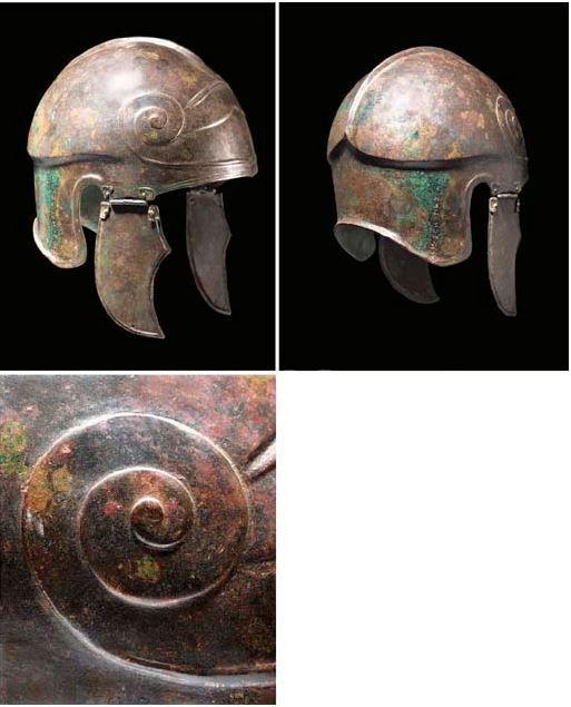 Chalcidian helmet, 5th-4th century B.C. The domed crown with median ridge and carinated perimeter, a moulded spiral motif on each temple connected across the brow by shallow ribs, incised lines along edge below, a Greek dedicatory inscription down one side of rear neck-guard and highlighting of inscription, 24.1 cm high excl. cheekpieces. Private collection, from Christie's auction