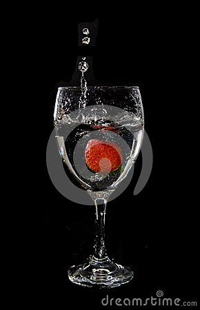 Strawberry splashing into a wine glass, clear, transparent liquid isolated on black background.