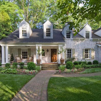 I adore the white brick with the green shutters, as well as the windows, wooden door, porch, brick pathway, and shrubbery. I'm not sure how I feel about the bricks being lime-washed, though.