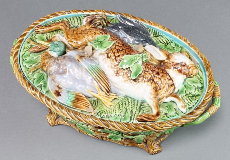 "Lot 20, A Victorian Minton Majolica oval game pie dish and cover, the lid decorated with a hare, swallow and blackbird, the basket weave base with acorn decoration and twin handles. Pattern 899, 13""w, est £100-200"