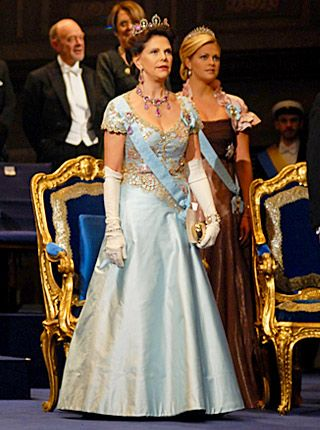 Queen Silvia at the 2008 Nobel Prize Award Ceremony in an ice blue silk evening gown with laces in pink and gold, designed by Jacques Zehn...