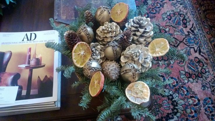 Composizione natalizia realizzata con abete argentato, arancio, e pigne dorate.