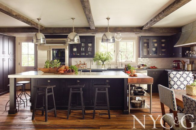 Exposed beams and rough-hewn floors combine with state-of-the-art appliances, creating a kitchen that's both industrial and rustic, with a vintage-farmhouse feel.