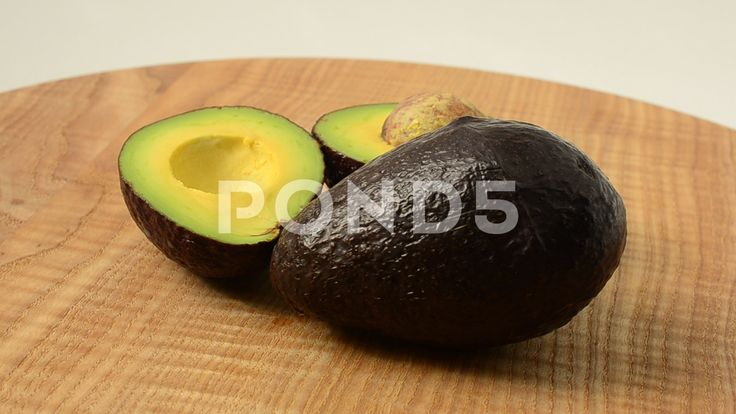Avocado on a wooden board.   #avocado #board #closeup #rough #ripe #two #slice #delicious #tropical #green #white #fat #sweet #diet #brown #organic #shot #bright #studio #light #salad #clipping #vegetable #macro #half #tasty #lifestyle #healthy #seed #nice #good #cut #plant #skin #wooden #fruit #background #path #fresh #nutrition #health #pear #nature #perfect #exotic #chopping #food #eating