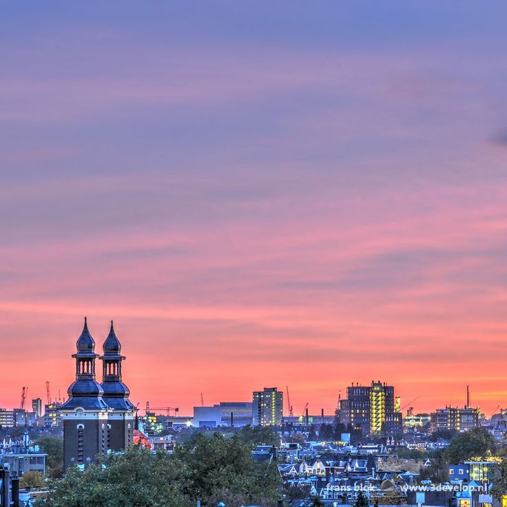 An evening sky in fifty shades of purple above the Old West in Rotterdam, with on the left the two towers of Paradise Church on Nieuwe Binnenweg. A little further in the background also cranes and chimneys in the port district are visible.