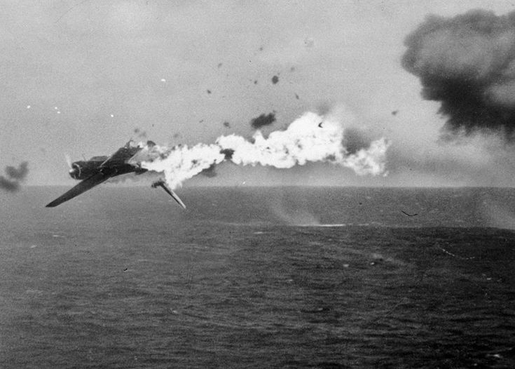 A Japanese torpedo bomber goes down in flames after a direct hit by 5-inch shells from the aircraft carrier USS Yorktown, on October 25, 1944.