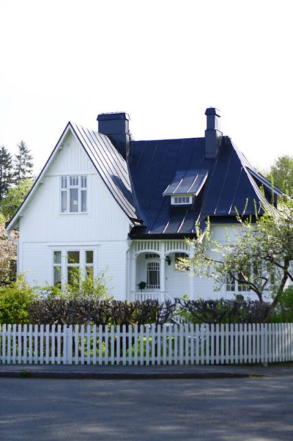 I love this little country villa - with the concave navy blue tin topping off the white clapboard. So cute!