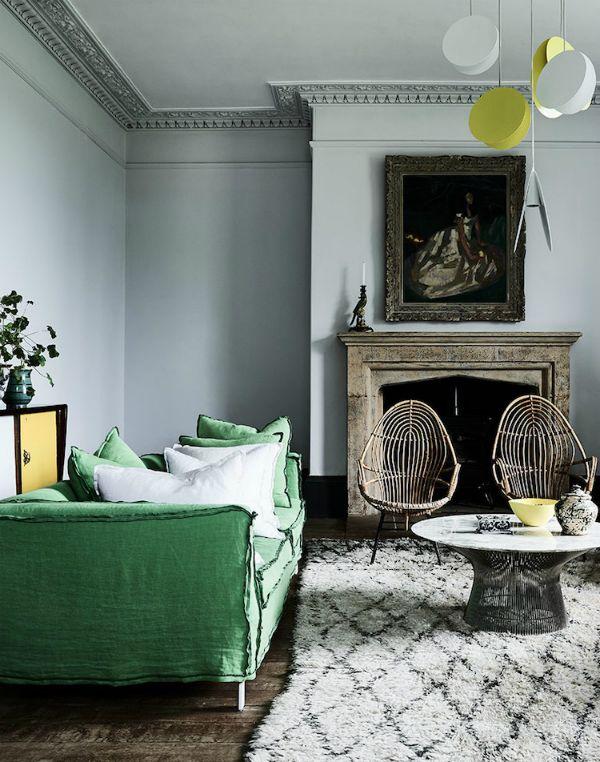 salón con paredes pintadas en gris azulado; sofá en verde esmeralda