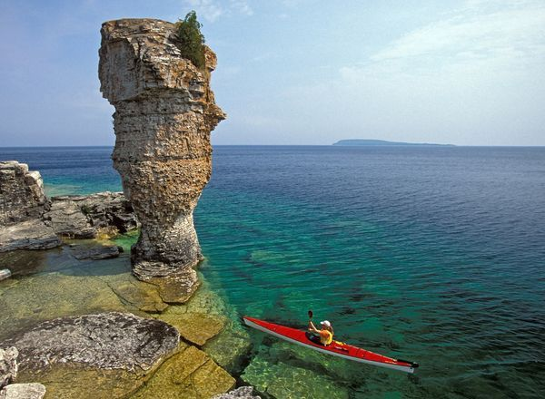 A sea kayaker navigates the rocks around Flowerpot Island in Ontario's Fathom Five National Marine Park. Located on Lake Huron, Fathom Five is a marine conservation area popular with divers and paddlers and for its island boat cruises.