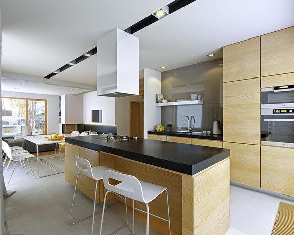Kuchnia z perspektywy okna - bardzo fajne połączenie drewna i czarnych blatów kuchennych.