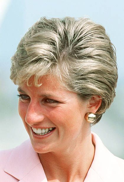 The Princess of Wales wears a new short hairstyle during a visit to Inverness in Scotland, July 1990. She wears a pink Catherine Walker suit.