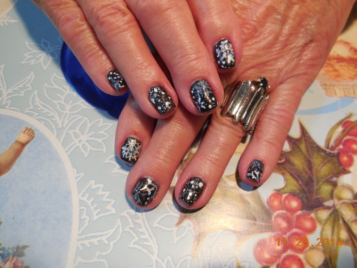 Snow Flakes in grey and white on black.  Nail Art by Cynthia Laughlin