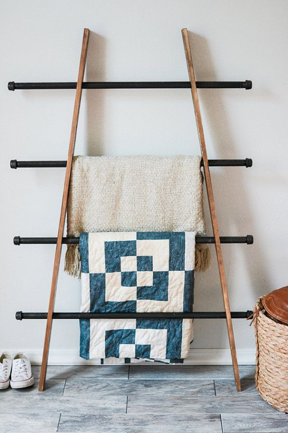 This industrial blanket ladder features stained wood and piping. Its the perfect rustic accent to keep your blankets, quilts, and afghans organized and beautifully on display.  The ladder can lean in at an angle as pictured, or the wood can easily be adjusted to sit straight up and down. There are holes in the wood that are made to fit the iron pipes. The pipes are *not* adhered to the wood, which makes adjusting the blanket ladder very simple.  The wood is stained and finished with a thick…