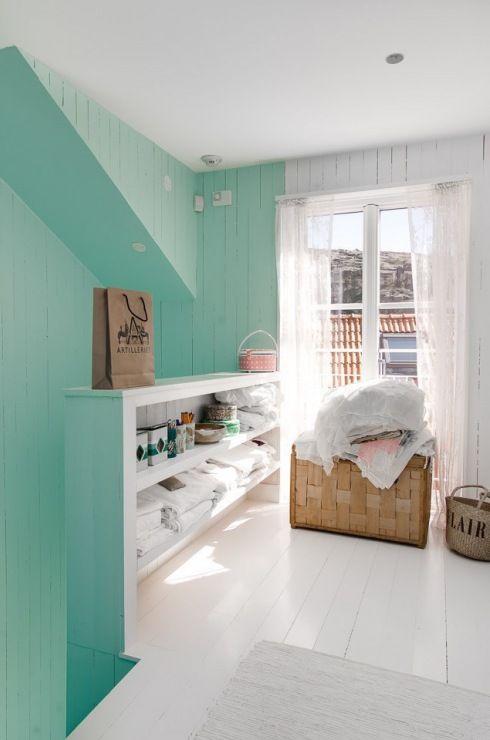 miętowe i białe deski na ścianie w skandynawskim domku nad fiordami
