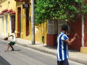 Es un partido de béisbol en Bogotá, Colombia. El partido de béisbol es en un calle.