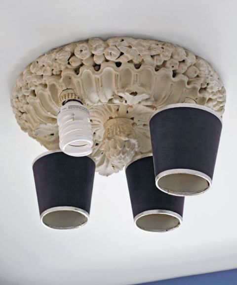 He outfitted this VINTAGE FIXTURE  with green compact fluorescent bulbs, then sleeved them with dark shades to warm the light they provide.