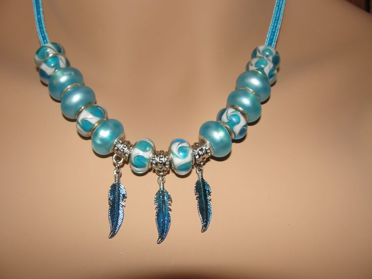 Necklace with turquoise glass beads and blue over silver feathers strung on parachute rope with adjustable length.