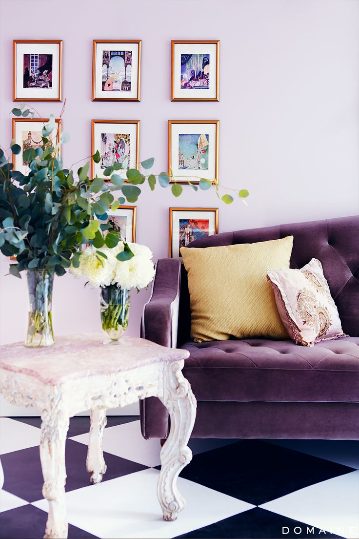 Purple living room with gallery wall, antique side table, floral arrangements, tufted sofa, and black and white tiled floor