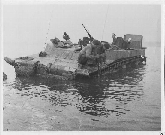 Members of the Princess Patricia's Canadian Light Infantry freeing the tracks of a Buffalo amphibious vehicle that have become fouled with wire found on the bank, while establishing a bridgehead across the river IJssel. North of Zutphen, Netherlands. April 11, 1945.