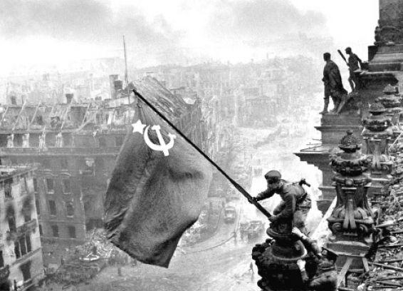 Fotografía de un soldado de la ex Unión Soviética colgando la bandera con la hoz y el martillo en la cúpula del Reichstag nazi de Berlín