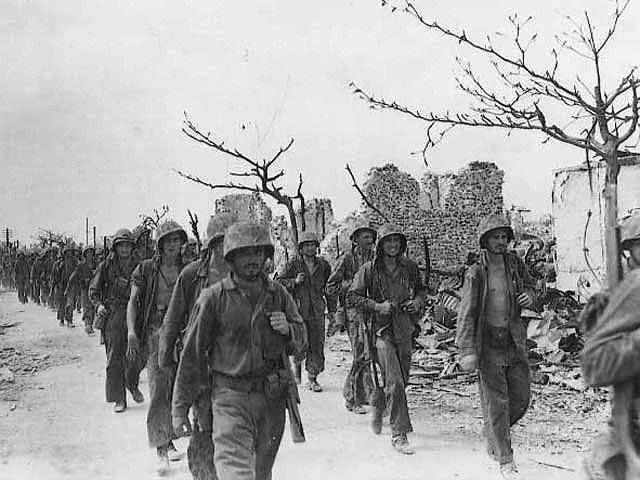US Marines marching through Garapan Saipan Mariana Islands 6 July 1944.