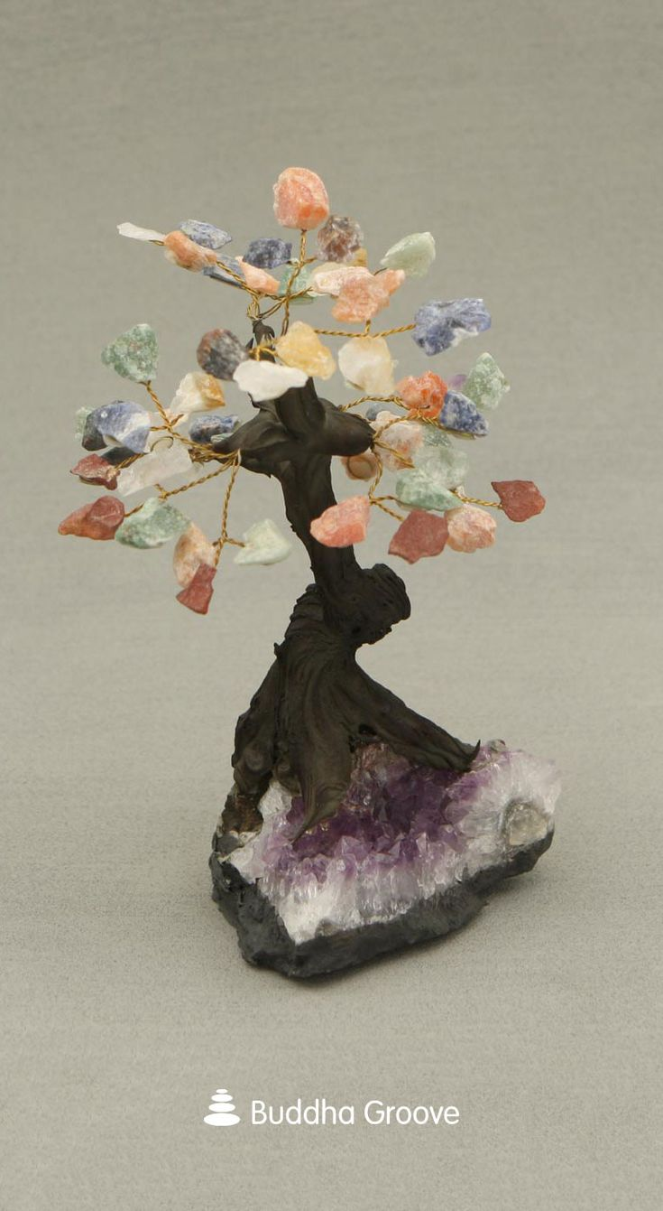 All of energies of blue calcite, green calcite, clear quartz, and more are featured in a single stunning piece. This tree's plethora of colored gemstones makes for both a marvelous display and a powerful healing tool. An amethyst base adds a little bit of extra protection, as amethyst is said to shield the user from negative energy.