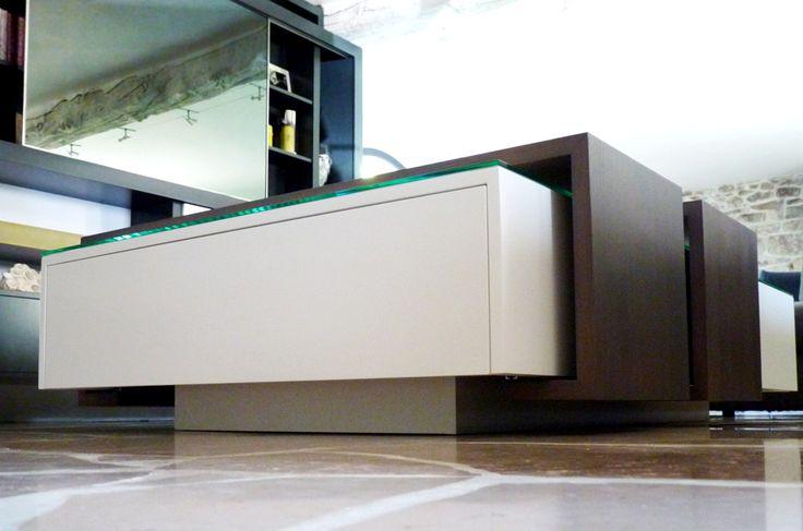 Une table basse au design épuré qui cache bien son jeu. Chemins de table en bois, coulissants pour une utilisation modulable et un accès aux coffres et tiroirs. plateau en verre