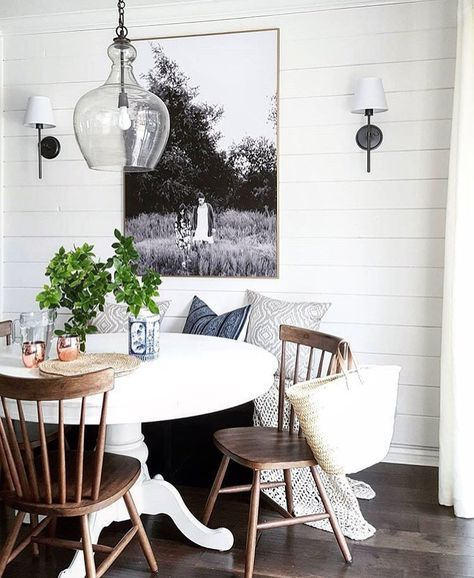 White pedestal table, wood chairs,sconces, b&w art