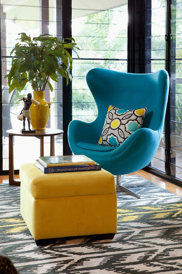 Contemporary armchair in aqua woollen fabric. Custom-made rug, ottoman and side table with accessories.