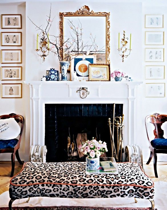 Leopard cushioned table and fireplace with collected objects on mantel.