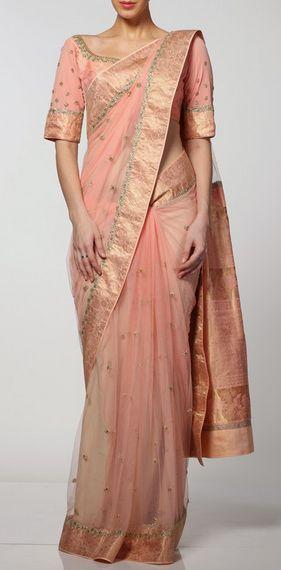 An elegant salmon pink net saree with kanjivaram borders in gold and pink. The saree has a kanjivaram pallu and is embellished with zardozi work with sequin highlights. The saree is worn with a salmon pink kanjivaram blouse with pink net sleeves embellished with zardozi and sequins. Designer: Neeta Lulla