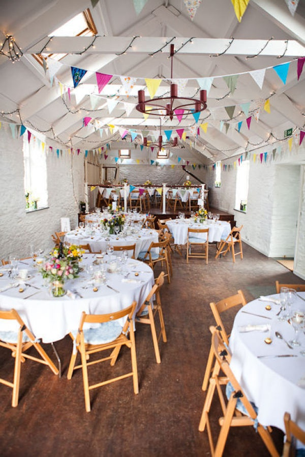 Colorful bunting adorned this English countryside reception space. Photography by greenphotographic.com, Floral Design by thebluecarrot.co.uk
