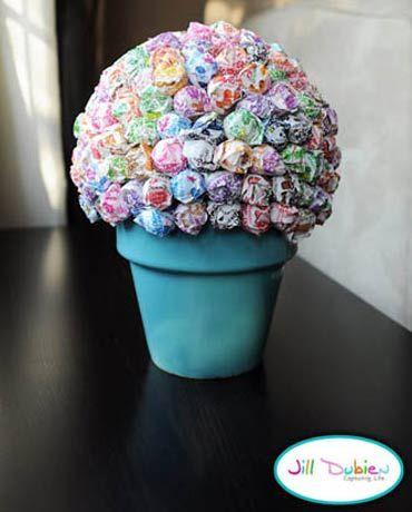 A árvore de pirulito pode ser usado como centro de mesa em festas infantis ou para surpreender a criançada em qualquer situação.  Espete os pirulitos na bola, mantendo-os bem unidos, até preencher a parte da bola que ficou fora do vaso.