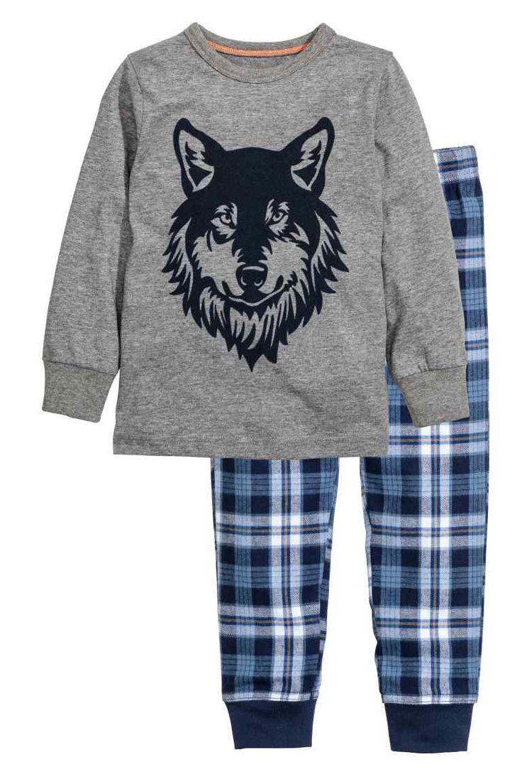Pyjama: Een zachte pyjama. Een tricot trui met een print vooraan en een ribboord onder aan de mouwen. Een broek van katoenflanel met elastiek en een trekkoord in de taille en een ribboord onder aan de pijpen.