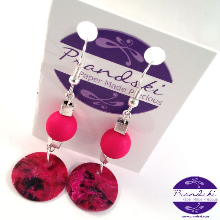 Silver plated dangle earrings.With pink acrylic bead and pink coloured mussel shell disc.     • Twopink acrylic beads and pink coloured mussel shell charms. • Silverplated ear wire hooks...