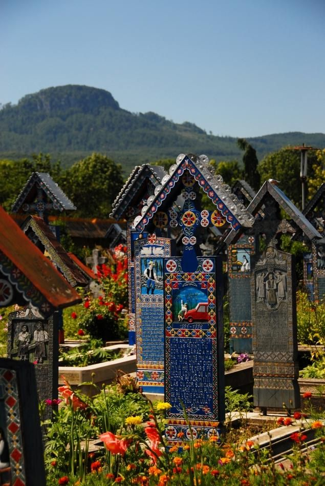 "The gravestones in Sapanta's Cimitirul Vesel, or ""Merry Cemetery"" are brief glimpses into the lives of the people they immortalize. Over 1,000 blue wooden crosses have crowded into this cemetery, each illustrated with a bright, colorful picture and a darkly-humorous poem."