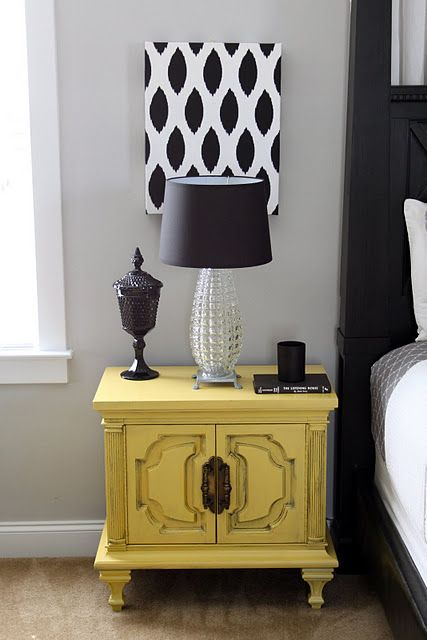 Combo of vintage and modern - pretty do-able by spray painting a thrift store nightstand and making the wall art by covering a pizza box with fabric. The black amethyst covered jar is commonly found in antique shops.