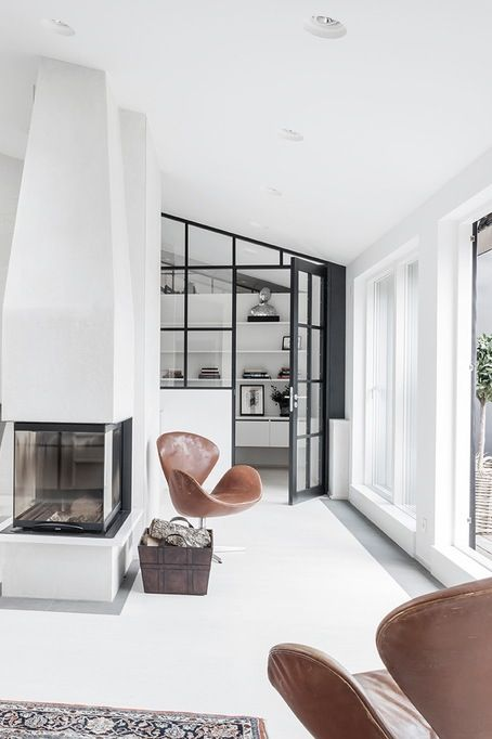 white interior with black details colorful carpet and tanned leather swan chair