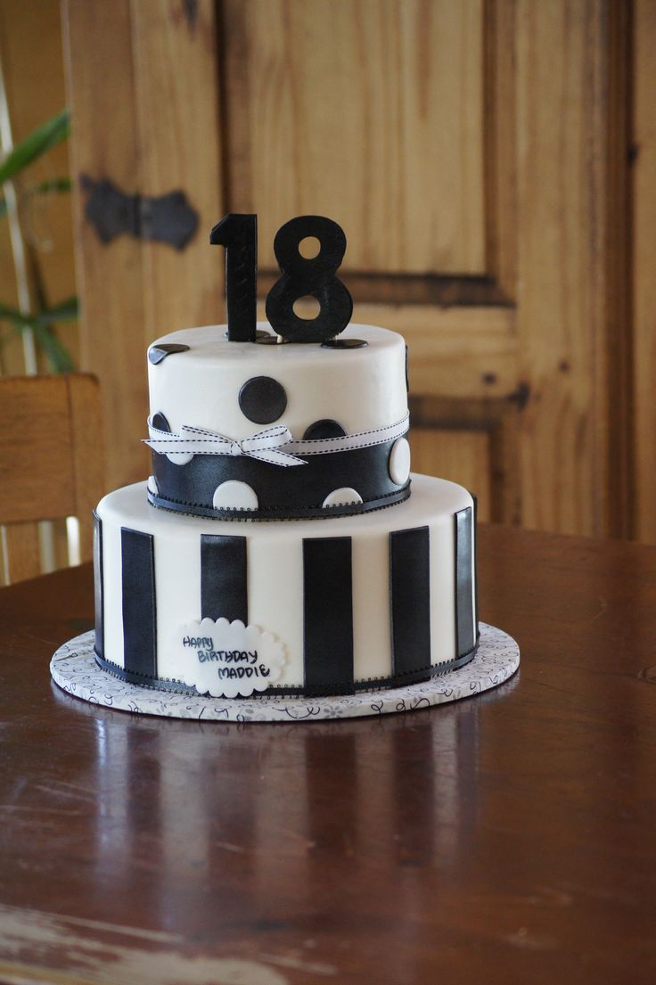 Tiered black and white birthday cake with polka dots and stripes