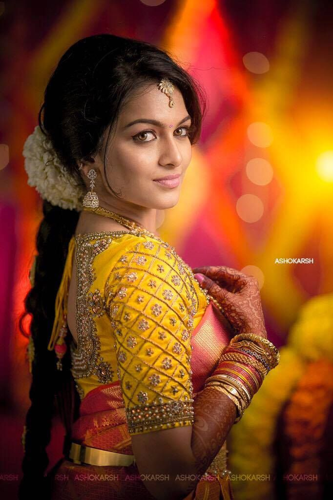 South Indian bride. Gold Indian bridal jewelry.Temple jewelry. Jhumkis.Orange red silk kanchipuram sari with contrast embroidered yellow blouse.Braid with fresh jasmine flowers. Tamil bride. Telugu bride. Kannada bride. Hindu bride. Malayalee bride.Kerala bride.South Indian wedding.