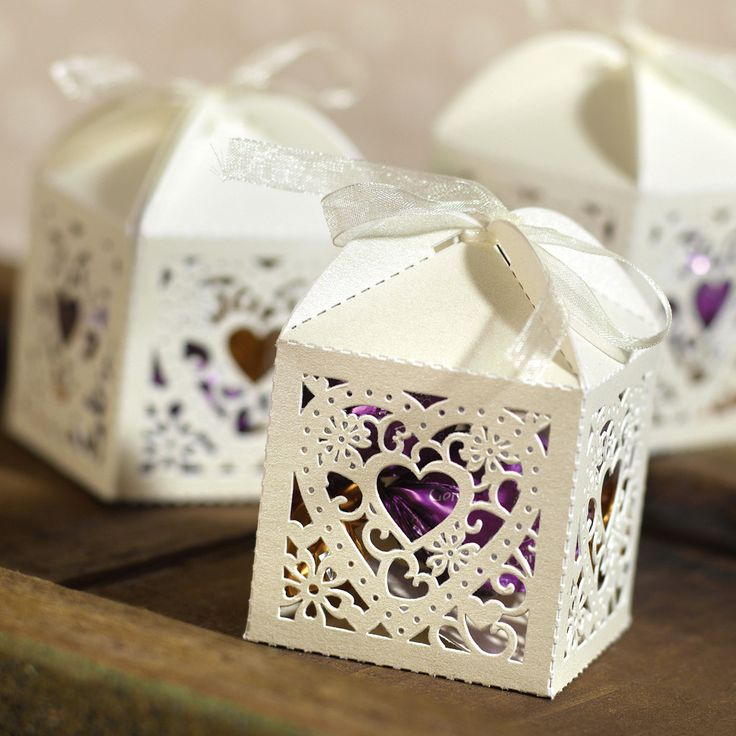 Decorative Ivory Wedding Favor Boxes with purple candies inside.