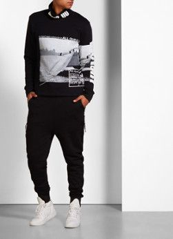 Sweater met fotoprint en col van Blood Brother. Deze bijzondere trui van het Britse streetwear label is bewerkt met diverse prints die refereren aan oude gevechten. De coltrui is daarbij afgewerkt met geribde zomen en een inkeping aan weerszijden voor extra comfort.