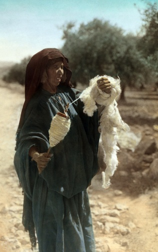 In Jericho, an elderly woman wears a veil and spins wool into yarn in Jericho, Palestine.