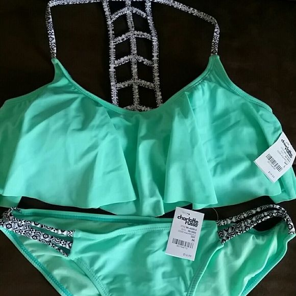 Charlotte Russe NEW WITH TAGS swimsuit Top is size large. Bottoms are size medium. Flounce bikini with ladder back. Straps on side of bottoms and back of top are Geo/tribal black and white. Charlotte Russe Swim Bikinis