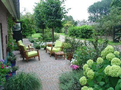 Onderhoudsvriendelijke landelijke tuin met afgeronde plantgedeelten.