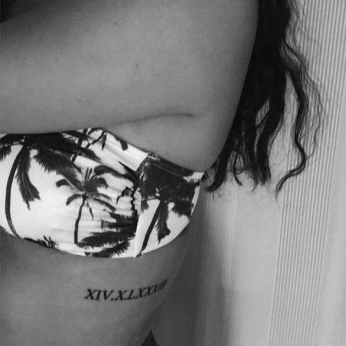 Little side tattoo of a date in roman numerals on Junie.