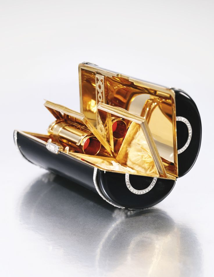 Enamel and diamond vanity case, Cartier, circa 1920 The black enamel case decorated with two lines of millegrain-set rose and single-cut diamonds, enhanced with palmette motifs and diamond thumbpiece, opening to reveal a cigarette compartment, a mirror, a lipstick holder and two powder compartments,  measurements approximately 85 x 40 x 30mm, signed Cartier, numbered, French assay and indistinct maker's marks.