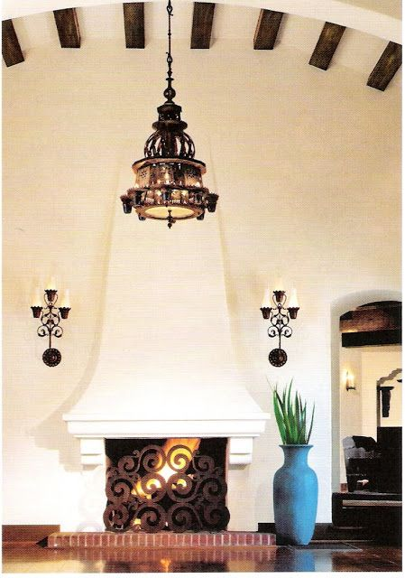 Spanish Colonial,  Nice arched  beamed ceiling.  Simple plaster fireplace. Great Hacienda Living room.  Looks very Old Hollywood. Cut metal fireplace screen.  Live Beautifully.