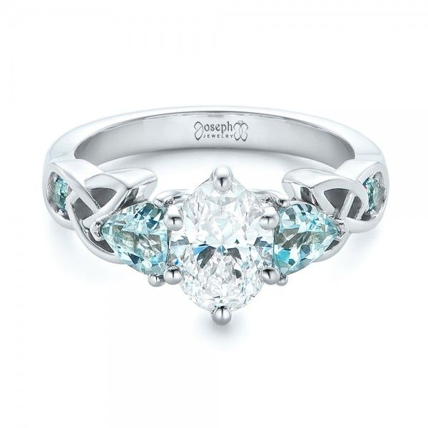 this exquisite engagement ring features an oval solitaire diamond flanked by trillion blue topaz