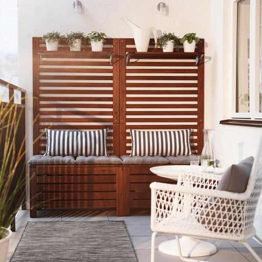 A balcony with brown wooden storage benches with seat cushions, wall panels and shelves filled with green plants